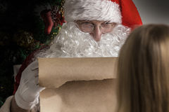 Santa Claus and girl. Santa Claus holding list on old paper and girl choosing gift Royalty Free Stock Images
