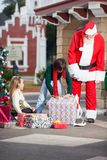 Santa Claus And Girl Looking At Boy Opening Gift Royalty Free Stock Photos