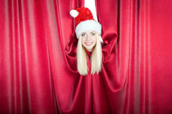 Santa claus girl looks out from curtain Stock Photos