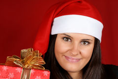 Santa Claus girl offering Christmas present Royalty Free Stock Photo