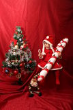 The Santa Claus girl, the oversized candy cane and the Christmas tree. Cute girl wearing a red Santa Claus costume wearing an oversized candy cane sitting next Stock Images