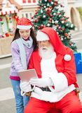 Santa Claus And Girl Using Digital Tablet Royalty Free Stock Images