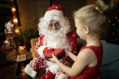 Santa Claus gives a gift to a child, but he likes him so much that he does not want to give it away