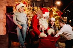 Santa Claus gives presents to children on Christmas Day. Santa Claus gives presents to children near the fireplace on Christmas Day stock photo