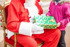 Santa Claus Giving Christmas Gift To Girl Stock Photography