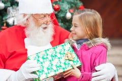 Santa Claus Giving Christmas Present To-Mädchen Lizenzfreie Stockbilder