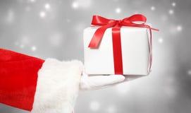 Santa Claus Giving ein Weihnachtsgeschenk stockfotos
