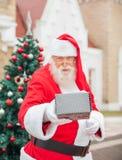 Santa Claus Giving Gift Against House Royaltyfri Foto