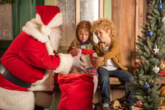 Santa Claus giving gift boxes to Children. From sack Royalty Free Stock Images