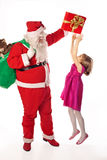 Santa Claus giving  gift. Little girl jumping and asking gift. E Royalty Free Stock Photos