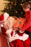 Santa Claus Giving Gift To Boy royalty free stock photography