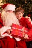 Santa Claus Giving Gift To Boy royalty free stock image