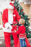 Santa Claus Giving Gift To Boy Royalty Free Stock Image