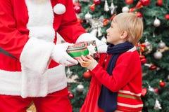 Santa Claus Giving Gift To Boy Stock Photo