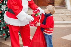 Santa Claus Giving Gift To Boy Stock Images