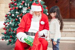 Santa Claus Giving Gift To Girl Stock Photography