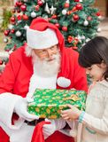 Santa Claus Giving Gift To Girl Stock Photos