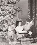 Santa Claus giving gift to little girl and her dog royalty free stock photos