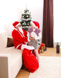 Santa Claus giving gift to a teen girl Royalty Free Stock Photography