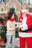 Santa claus giving a giftbox a young woman Royalty Free Stock Photos