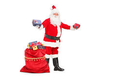 Santa Claus giving gifts and bag full of presents. Full length portrait of a Santa Claus giving gifts next to a bag full of presents  against white background Stock Photo