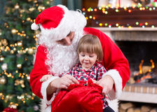 Santa Claus giving a present from sack to child Royalty Free Stock Photography