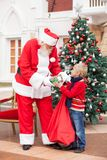 Santa Claus Giving Present To Boy Stock Image