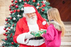 Santa Claus Giving Present To Girl Royalty Free Stock Images
