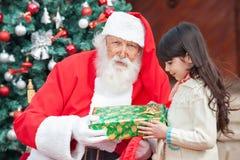 Santa Claus Giving Present To Girl Stock Photos