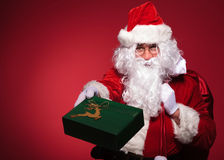 Santa claus is giving you a green present box Stock Photography