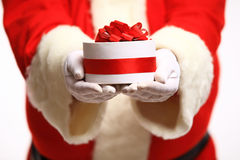 Santa Claus gloved hands holding gift box Stock Photos
