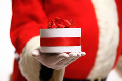Santa Claus gloved hands holding gift box Royalty Free Stock Photo
