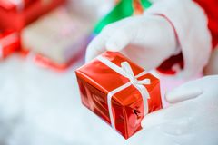 Santa Claus gloved hands holding gift box in room. Santa Claus brought gifts for Christmas and having a rest by the sofa. royalty free stock photo