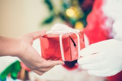 Santa Claus gloved hands holding gift box in room. Santa Claus brought gifts for Christmas and having a rest by the sofa. stock images