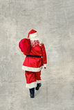 Santa Claus going with a bag of gifts. Royalty Free Stock Images