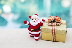Santa claus with gold gift box over blurred colorful background Royalty Free Stock Images