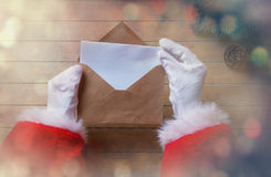Santa Claus got a Christmas letter. On wooden background Royalty Free Stock Image
