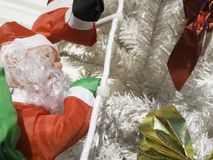 Santa Claus grimpe à un arbre Décorations d'un arbre de Noël Photo libre de droits