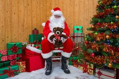 Santa Claus in a grotto giving you a teddy bear. royalty free stock photos