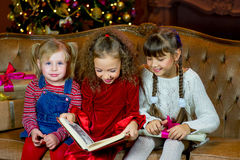 Santa Claus and group of girls reading a book Royalty Free Stock Photography