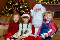 Santa Claus and group of girls reading a book Royalty Free Stock Image
