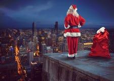 Santa Claus guarda dall'alto in basso la città che aspetta per consegnare i presente fotografia stock libera da diritti