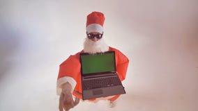 Santa Claus hält einen Laptop mit grünem Schirm und erregt Aufmerksamkeit zu ihr stock video
