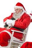 Santa Claus hållande bibel, medan koppla av på stol Arkivfoto