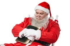 Santa Claus hållande bibel, medan koppla av på stol Royaltyfri Bild