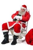 Santa Claus hållande bibel, medan koppla av på stol Arkivfoton