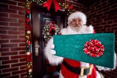 Santa Claus hållande gåvaask, Santa Claus behandskade händer som rymmer G Royaltyfria Bilder