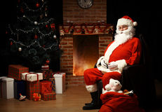 Santa Claus ha portato i regali per il Natale ed avere un resto Fotografie Stock Libere da Diritti