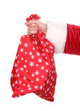 Santa Claus hand holding bag of gifts. Over the white Royalty Free Stock Photo
