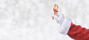 Santa Claus hand holding a candy cane over a silver bokeh background with snow effect. Banner size with copy space royalty free stock images